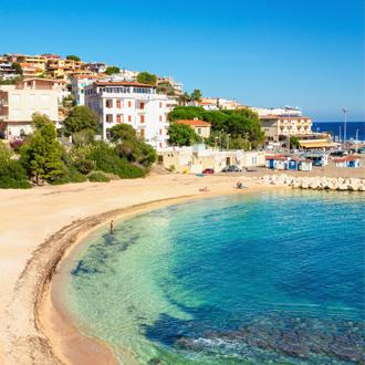 Foto van een goud zandstrand met blauw water en het dorpje Cala Gonone op de achtergrond