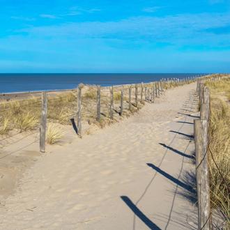Foto van een zandweg die naar de duinen leidt in Egmond Aan Zee