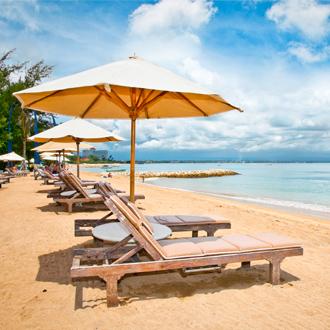 Ligbedjes met parasols op het strand van Sanur op Bali Indonesie