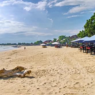 Strand op Benoa met parsols en palmbomen