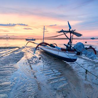 Vissersbootje met zonsondergang wat rood/roze kleurt in Benoa