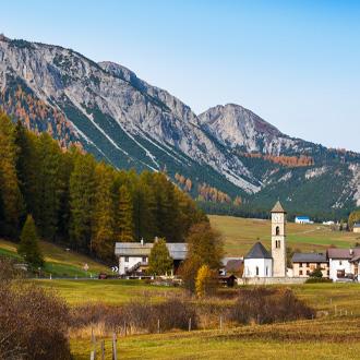 Groen landschap met hoge bergen in de horizon met een dorpje op de voorgrond.