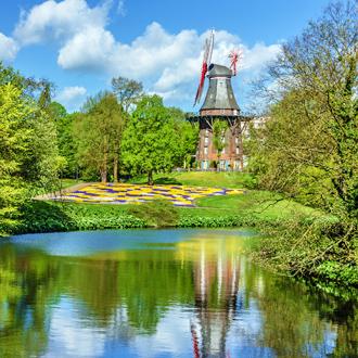 Foto van een molen in een groen park met meer in Bremen