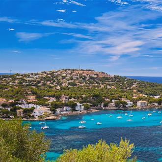 Panorama over Santa Ponsa, met bergen, blauwe zee en bootjes in de zee