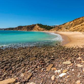 Strand Velhas in Cabanas, met blauwe zee en zandstrand en bergen op de achtergrond.