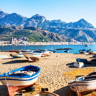 Het strand van Giardini Naxos, met gekleurde vissersbootjes en hoge bergen