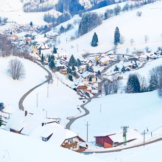 Sneeuw in een vallei met huizen Schwarzwald