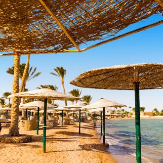 Zandstrand met parasols en palmbomen in Egypte