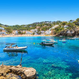 Vis en zeilboten in de helderblauwe zee bij Cala Vadella