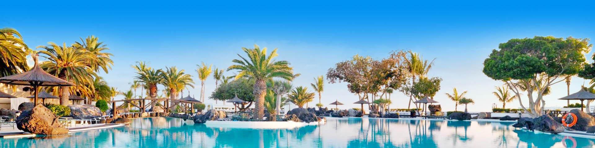 Prachtig Zwembad met wuivende palmboemen aan de de Canarische Eilanden