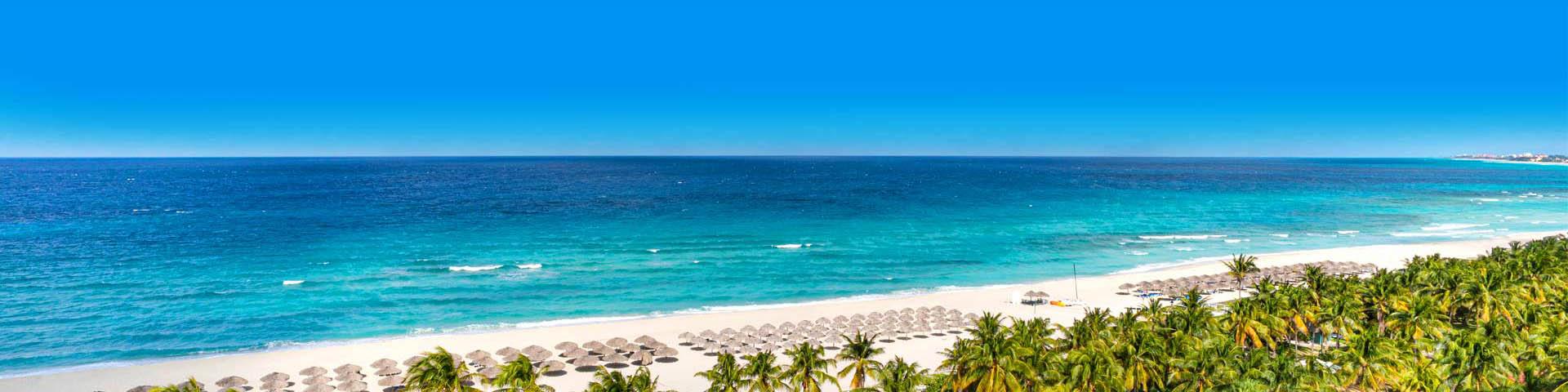 Uitzicht over palmbomen, wit zandstrand met rieten parasols en een helderblauwe zee op Cuba
