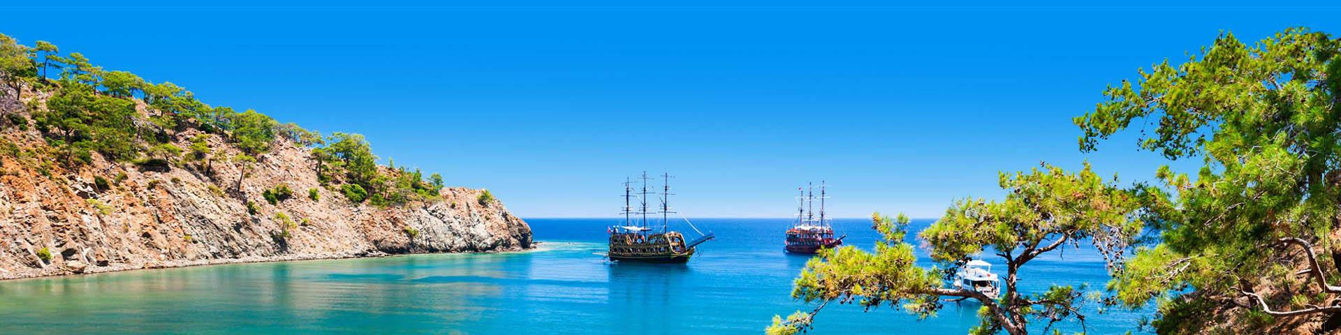 Uitzicht op de zee, rotsen en een oude boot bij Kemer in Turkije