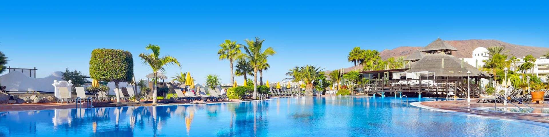 All Inclusive resort met groot zwembad, ligbedjes en palmbomen op Lanzarote