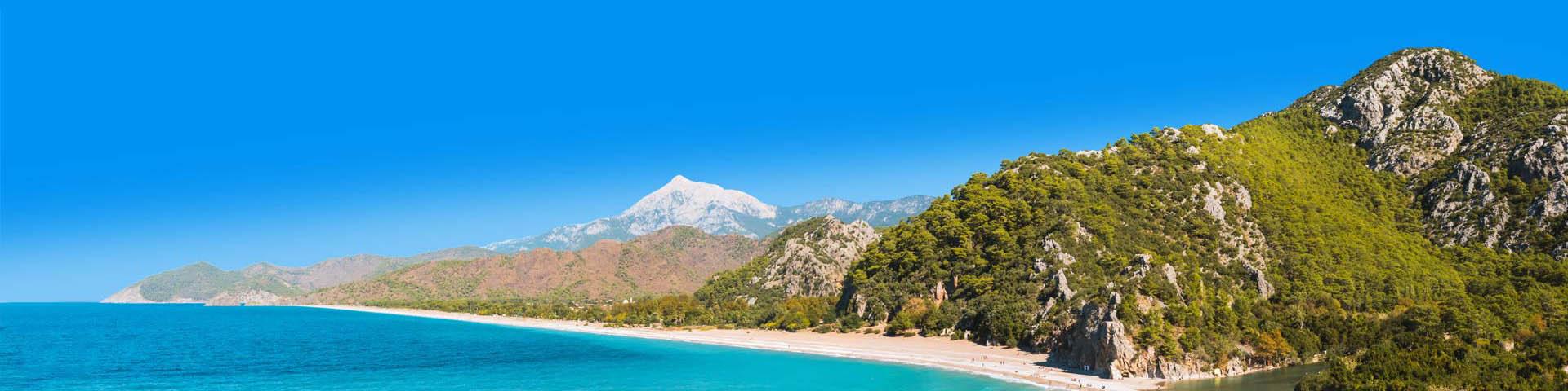 Kraakhelderblauwe zee met groene heuvelachtige rotsen aan de Lycische Kust van Turkije