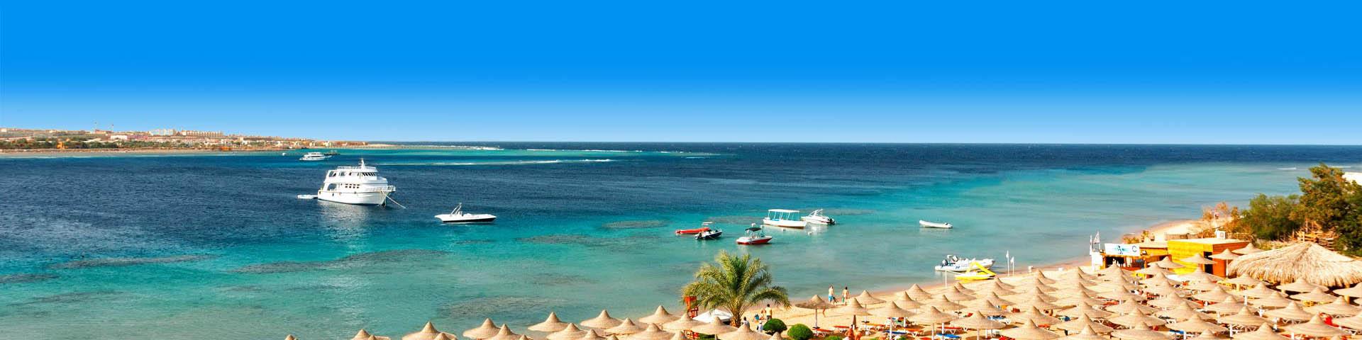 Uizicht over de blauwe zee en parasols in Makadi Bay
