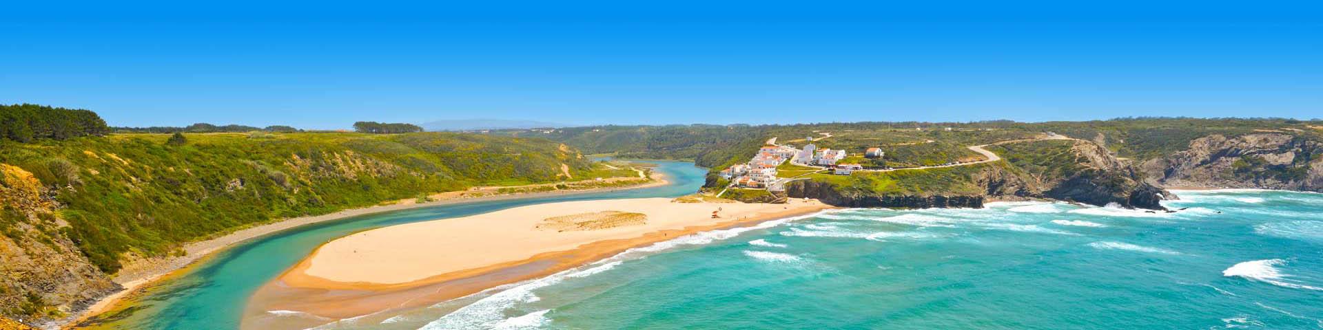 Heldere zee en goudgele zandbank met groene heuvelachtige rotsenen witte huisjes aan de kust van de Algarve, Portugal