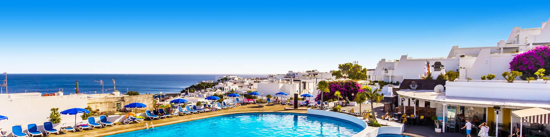 Een blauw zwembad en witte huisjes in Puerto del Carmen