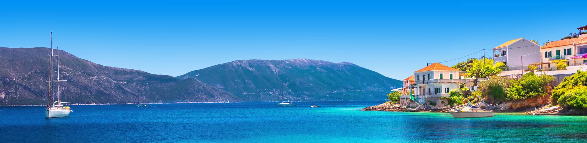 Uitzicht over turqoise helderblauwe zee met bootje en kust met Griekse huisjes in Griekenland