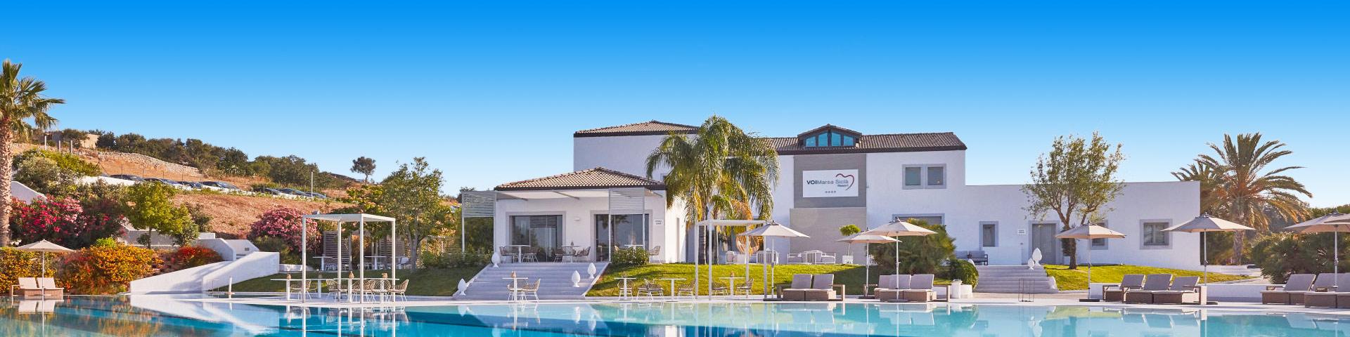 Wit hotel met zwembad en palmbomen in Italië