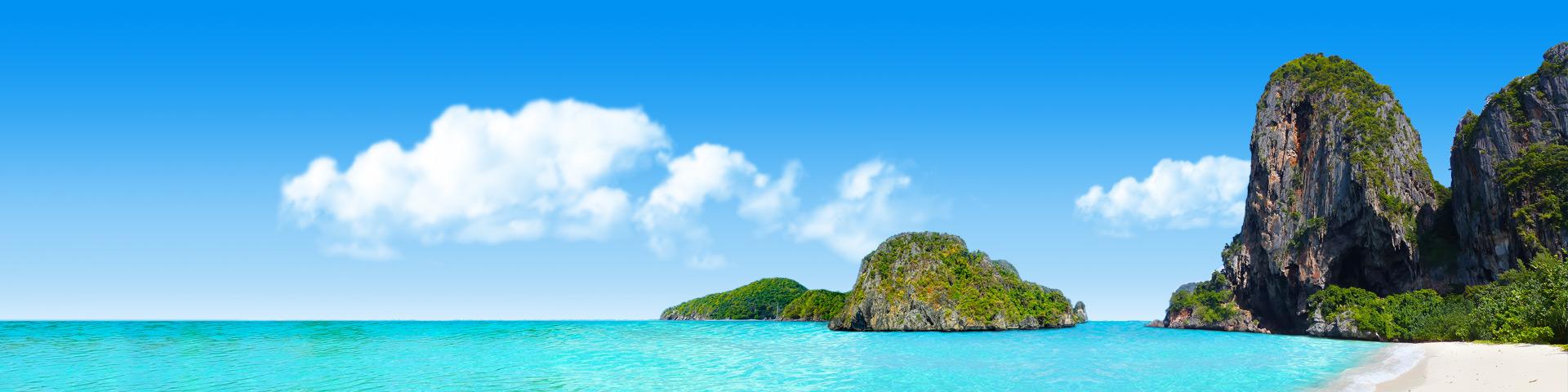 Strand met heldere lichtblauwe zee en rotsen in het water in Thailand