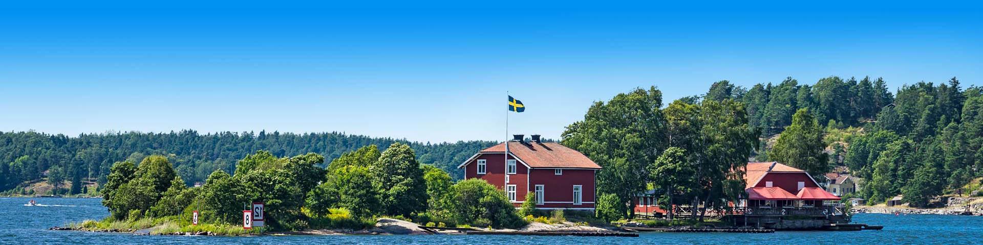 Groot meer met een klein rood huisje in Zweden.