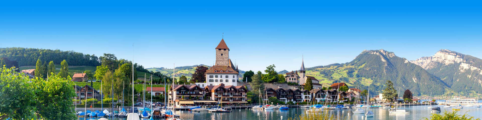 Haven met uitzicht op een kerk en in de verte groen landschap in Zwitserland.