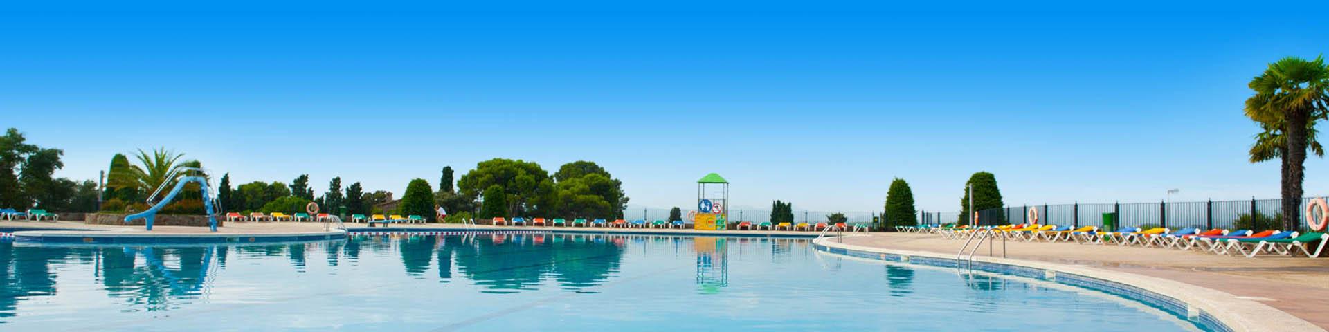 Zwembad op een camping met gekleurde ligbedjes en een glijbaan