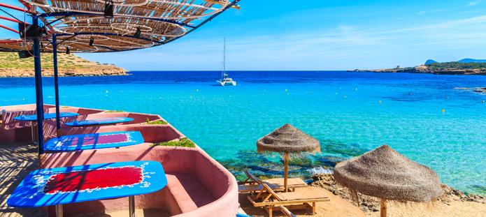 Uitzicht op helderblauwe zee met parasols op Ibiza