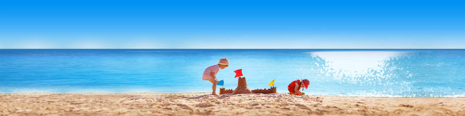 Kinderen spelen op het strand met een azuurblauwe zee als achtergrond