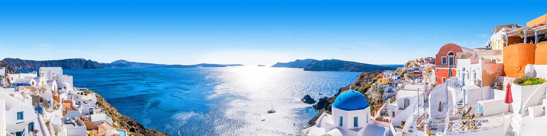 Witte en gekleurde huisjes in Santorini met een open blauwe zee