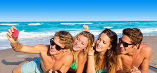 Jongeren maken selfie op strand in Egeïsche kust