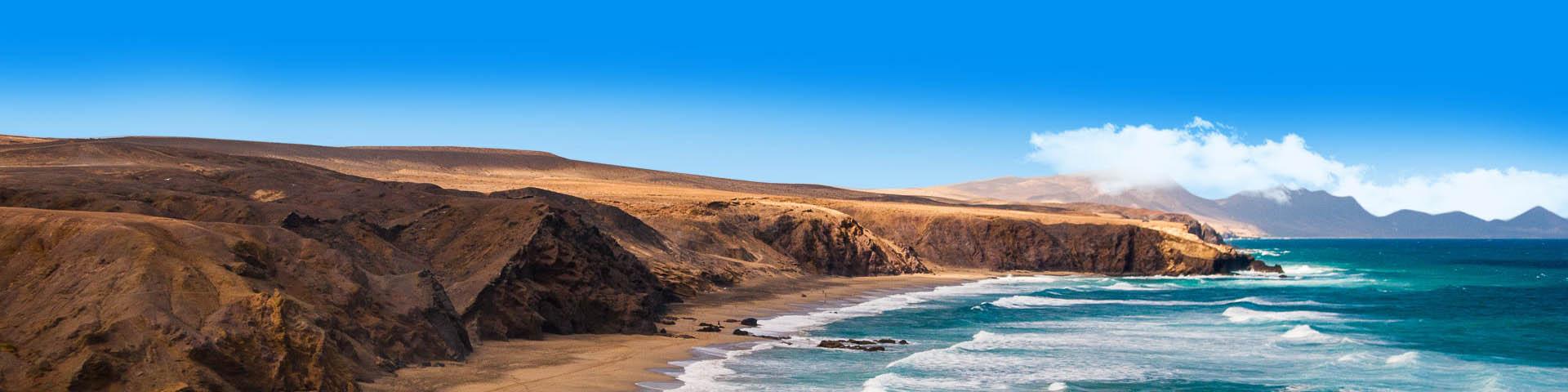De kustlijn van Fuerteventura met de zee en het landschap op de achtergrond