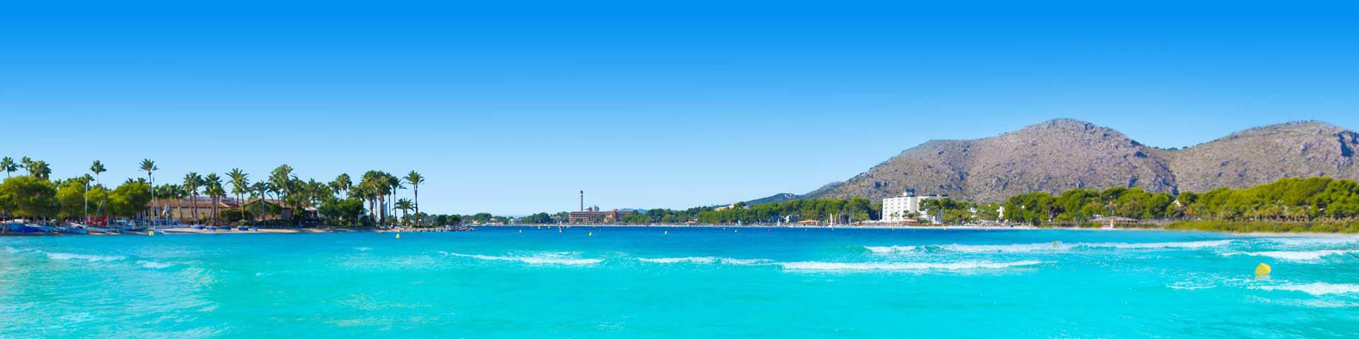 Kustlijn van Spanje met helderblauw zeewater en bergen op de achtergrond