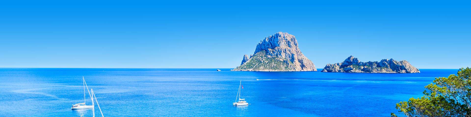 Kustlijn van Ibiza met helderblauw zeewater en een bootje op de voorgrond