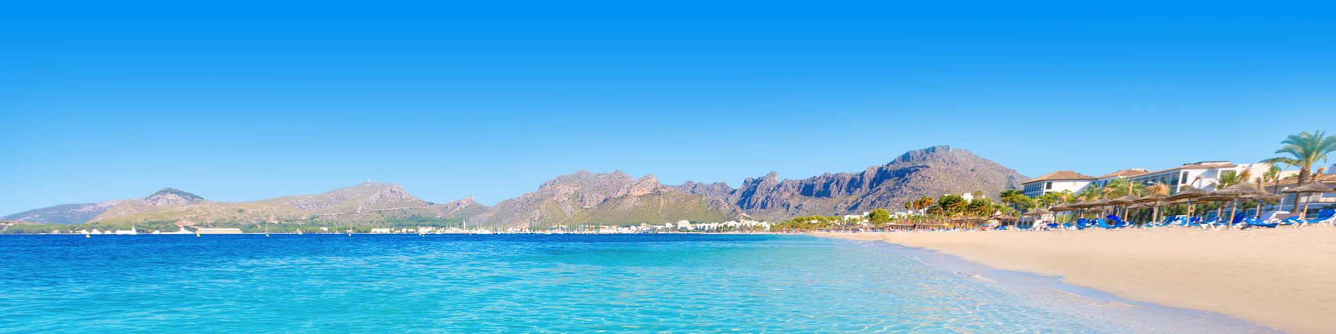 Helderblauwe zee met rotsen op de achtergrond aan de kustlijn van Mallorca