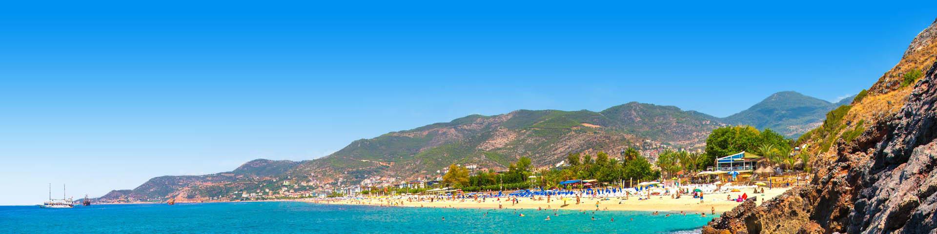 Strand met blauw water en bergen op de achtergrond