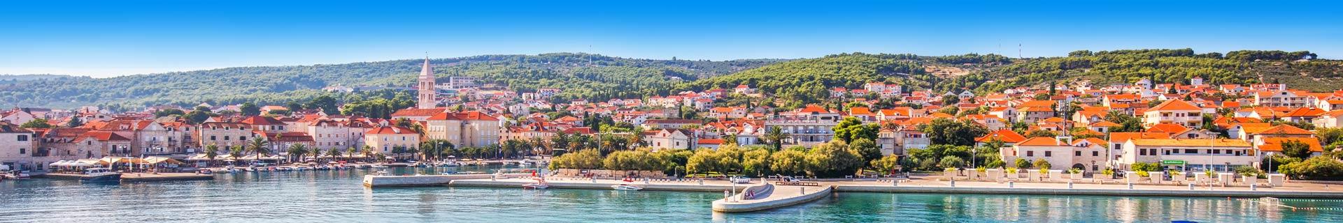 Uitzicht op helderblauw water en huizen met oranje daken