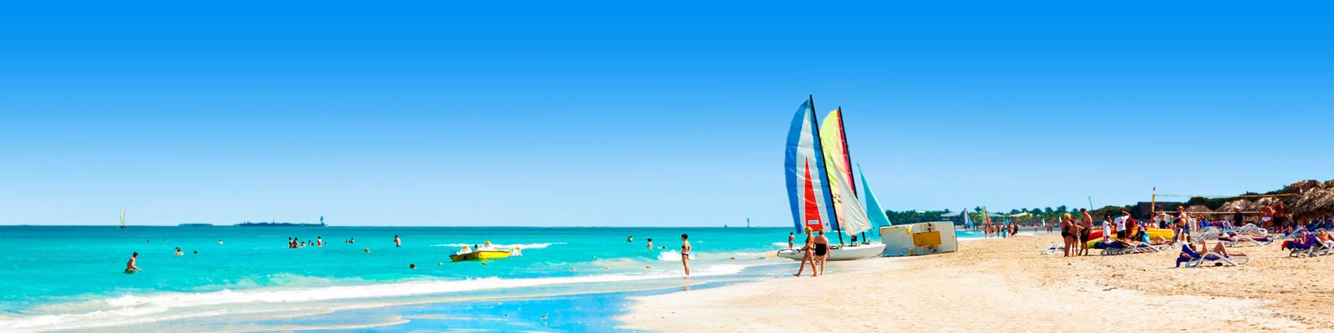 Wit zandstrand met azuurblauwe zee en vakantiegangers op het strand.