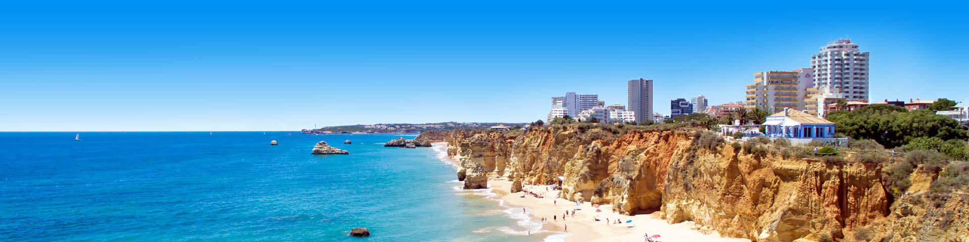 Prachtige Panorama van een Portugees strand met azuurblauwe zee, met bergen en stad in de verte.