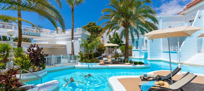 Verfrissend zwembad bij een hotel met palmboom op de achtergrond