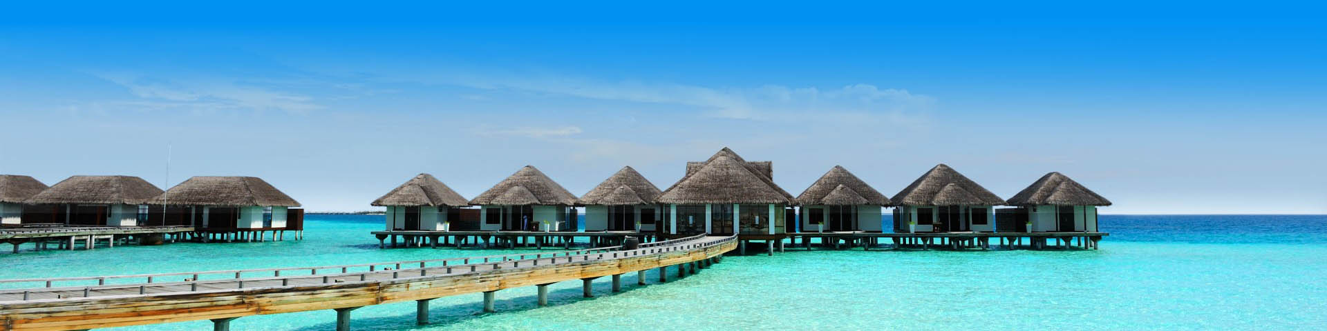 Waterbungalows aan een stijger gelegen in de helderblauwe zee van de Malediven