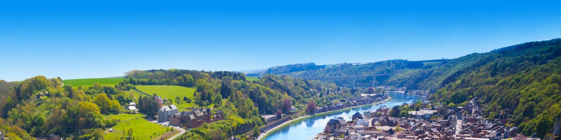 Uitzicht over groen heuvelachtig landschap met rivier dat door een stad loopt in België