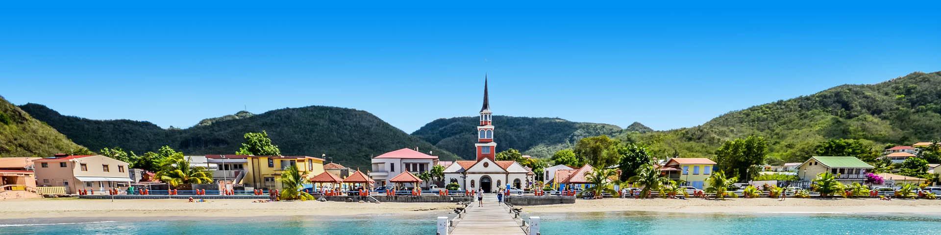 Een stadje aan zee met wit kerkje en groene bergen in Frankrijk