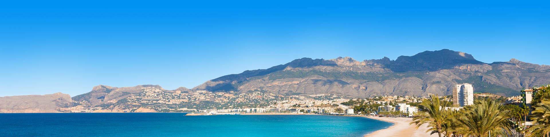 Zandstrand met blauw water en uitkijkend op gebergte in Spanje