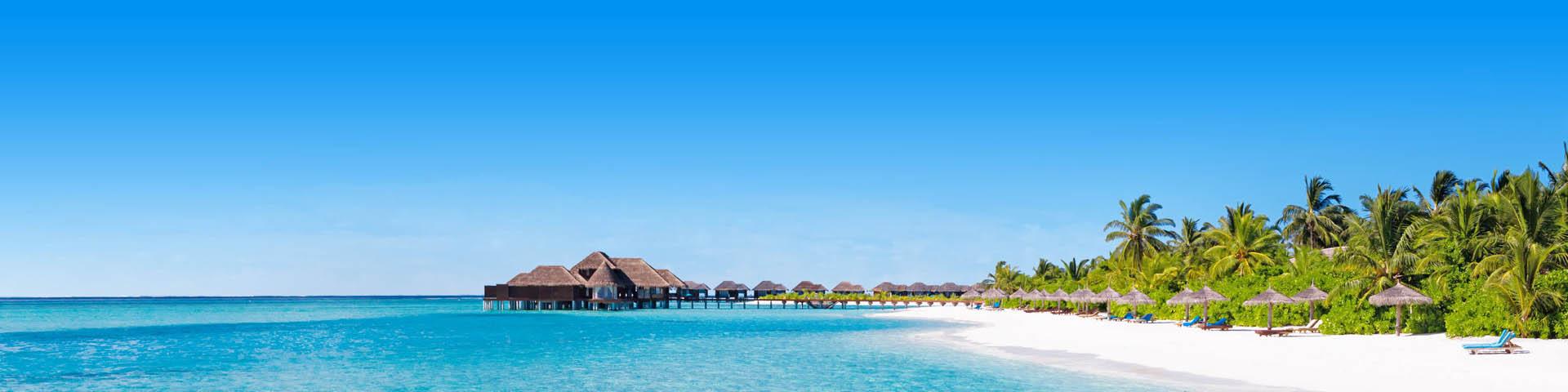 Prachtig wit zandsttrand met huisjes zwevend op de azuurblauwe zee