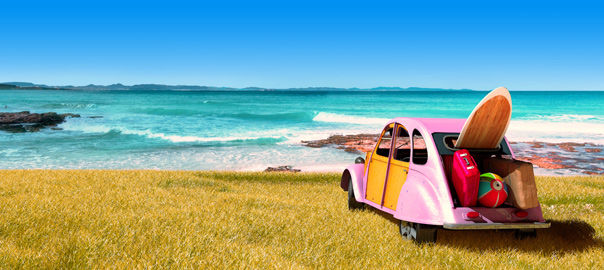 Roze auto met surfplank en strandspullen aan zee