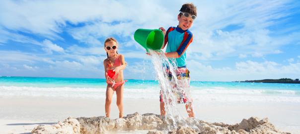Twee kids in zwempak op het strand op vakantie