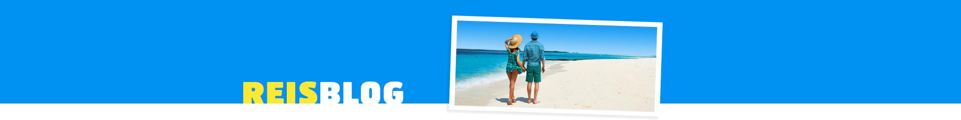 Een stel lopend over het strand met uitzicht over de blauwe zee en strand.