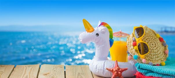 Opblaasbare unicorn met strandspullen en de zee