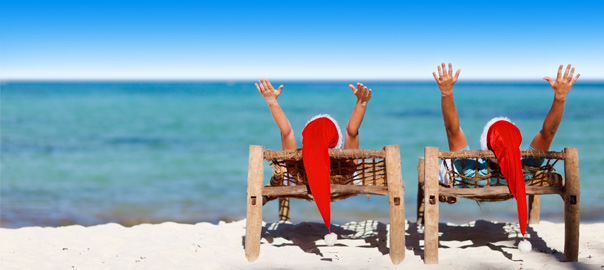 Twee vakantiegangers op het strand met kerstmutsen op